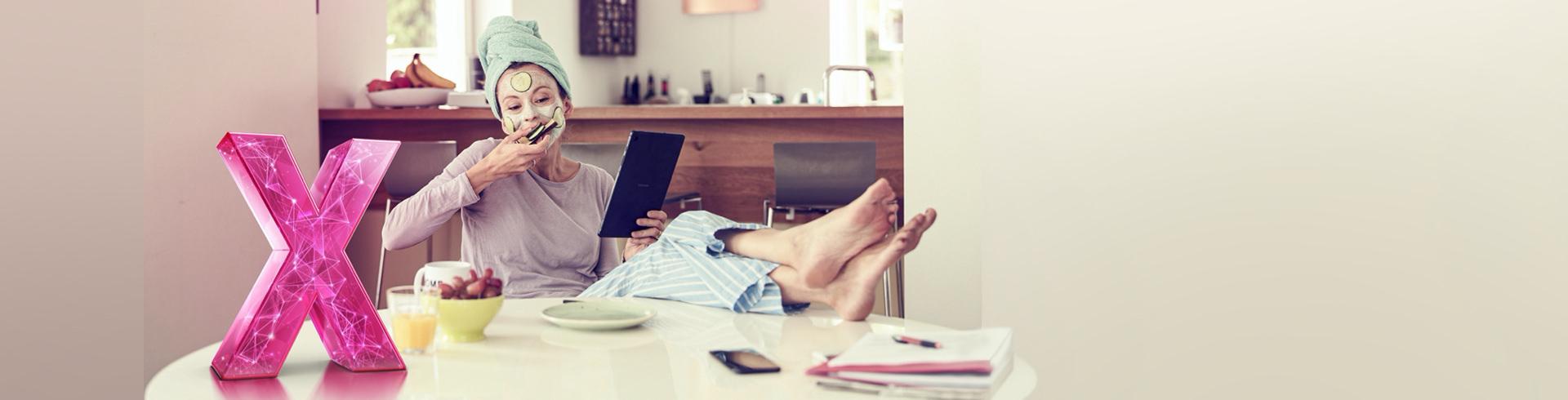 Frau sitzt mit Tablet im HomeOffice